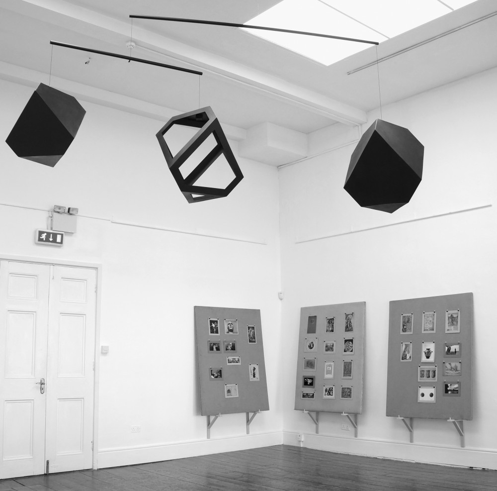 The Other Dark. Installation shot. Sirius Arts Centre, Cobh (2017). Works featured: Jeremy Millar: Melancholy Mobile (2017). Wood, paint. Jeremy Millar: The Man Who Looked Back (2010). Oak display stands, hessian-covered display screens, archive photographs and film stills mounted on card, clips, pins. Courtesy of the author and the Sirius Arts Centre.