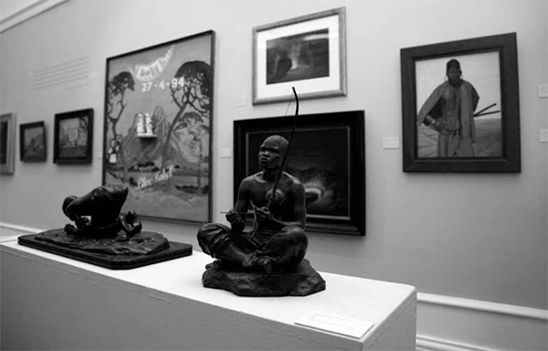Installation View Pierneef to Gugulective. Anton van Vouw's bronzes The Musician and the Dagga Smoker from 1907 set against Wayne Barker's painting Blue Colonies (1995) and Pierneef's Karibib (1924) in the background at left. Photo by Carina Beyer – © Iziko Museums.